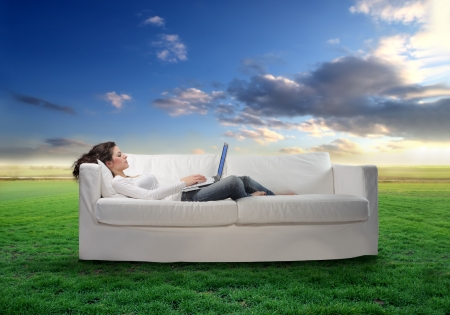 Young woman lying on a sofa with a laptop with green meadow on the background