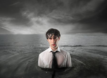 Wet businessman standing in the water with stormy sky on the background