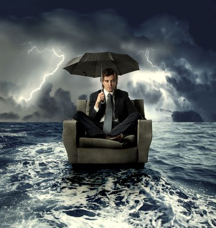 Businessman sitting under an umbrella on a sofa with sea on the background