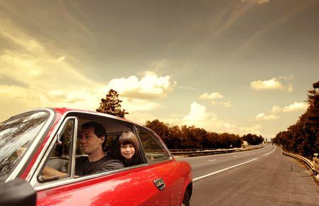 Foto de Young man driving a car with his daughter sitting behind him - Imagen libre de derechos
