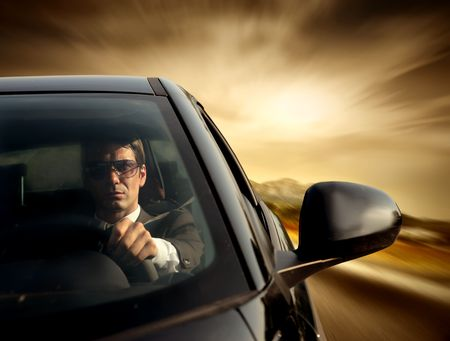 Businessman wearing sunglasses while driving his car