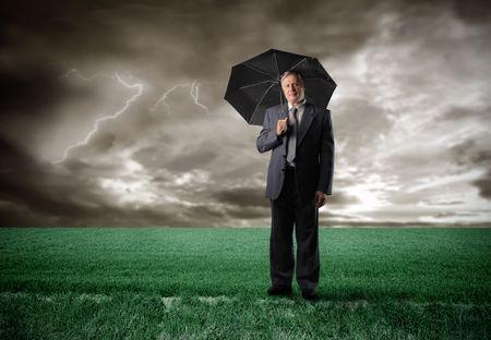 Senior businessman under an umbrella