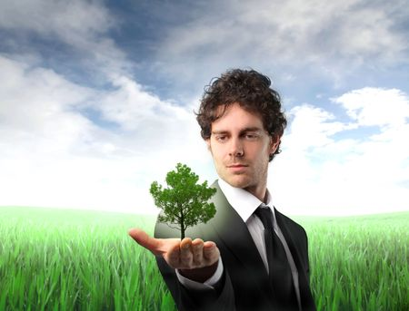 Businessman holding a tree in his hand