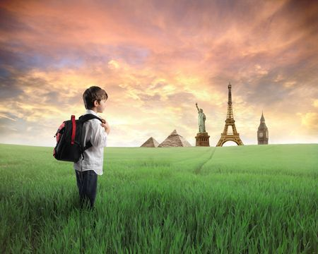 Child with rucksack standing on a green meadow with landmarks of diverse countries on the background