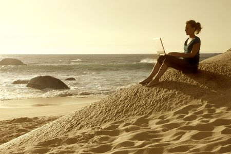 Young woman sitting on a beach and using a laptop