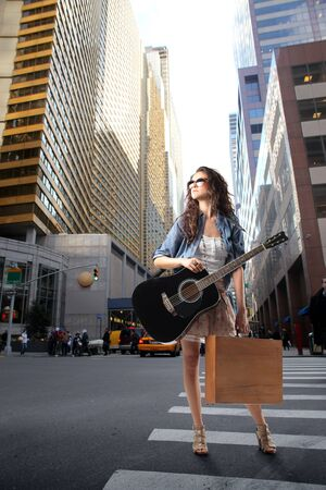 Photo pour Young woman carrying a shopping bag and a guitar standing on a city street - image libre de droit