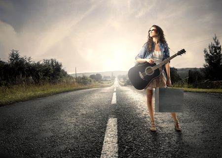 Young woman carrying a shopping bag and a guitar standing on a countryside road