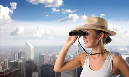 Smiling woman using binoculars with cityscape on the background