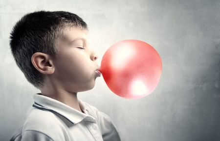 Child making bubbles with a chewing-gum
