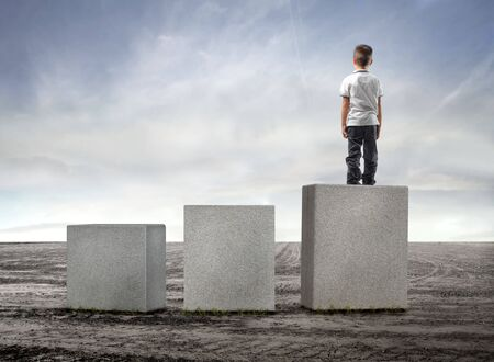 Child standing on the highest of three cubes in a field