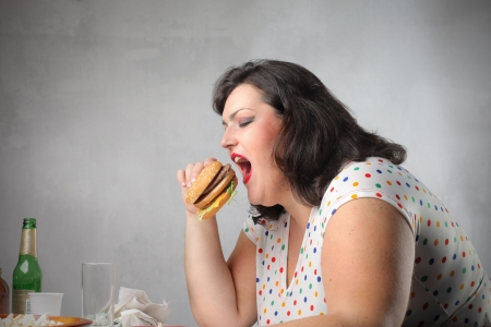 Fat woman eating junk food for dinner