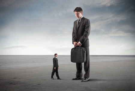 Tiny businessman impressed by a giant one standing next to him