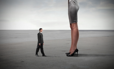 Tiny businessman standing in front of a giant woman's legs