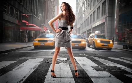 Foto de Beautiful elegant woman standing in the middle of a city street - Imagen libre de derechos