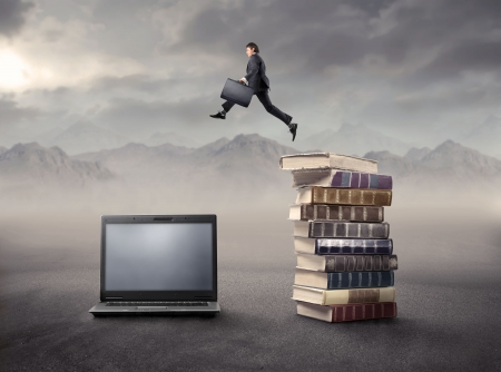 Businessman jumping froma stack of books on a laptop