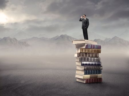 Businessman standing on a stack of books in the mountains and using binoculars