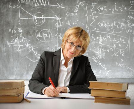 Teacher writing on a register in a classroom