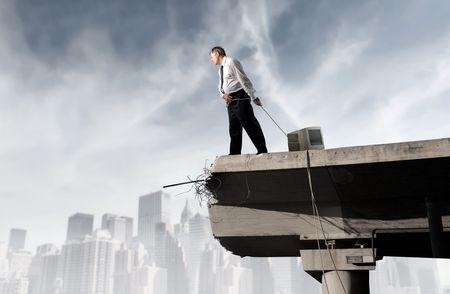 Businessman dragging a computer monitor on a bridge
