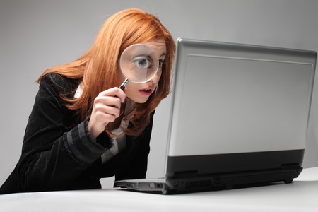 Young businesswoman observing a laptop with a magnifying glass