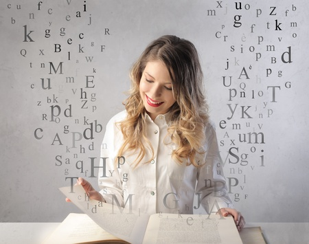 Smiling beautiful woman reading a book with letters flying away from it