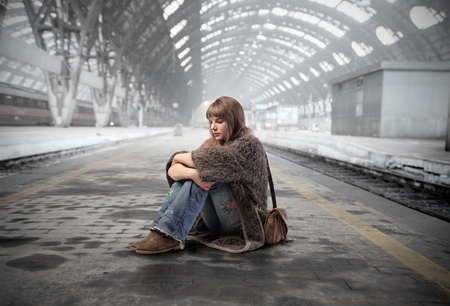 Young woman sitting on the platform of a train station