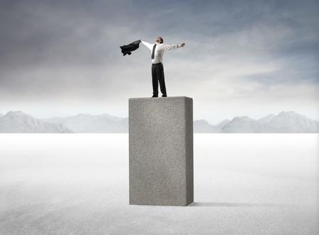 Businessman triumphing on a high cube