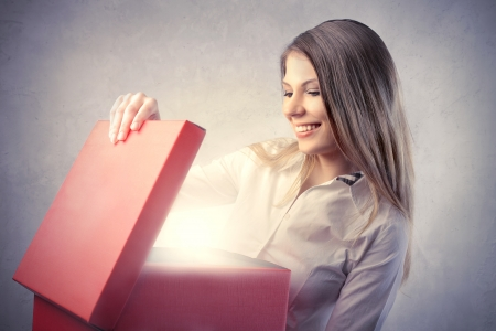 Smiling beautiful woman opening a gift