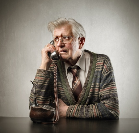 Worried senior man talking to telephone