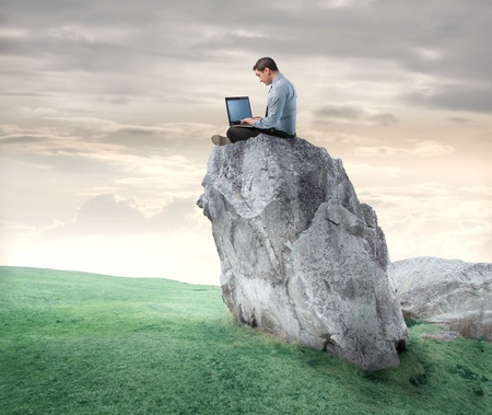 Photo for Businessman sitting on a rock and using a laptop - Royalty Free Image