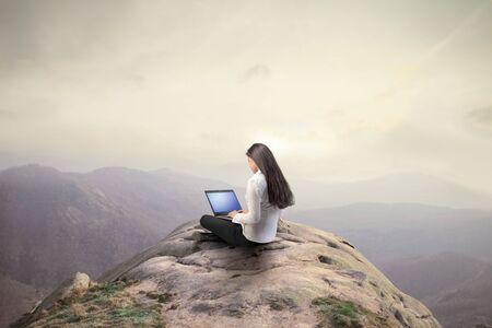Businesswoman using a laptop on the top of a hill