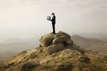 Businessman holding the Earth in his hands on a mountainの写真素材
