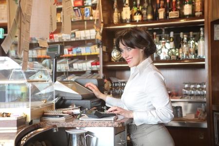 Photo pour Smiling waitress printing a bill in a bar - image libre de droit