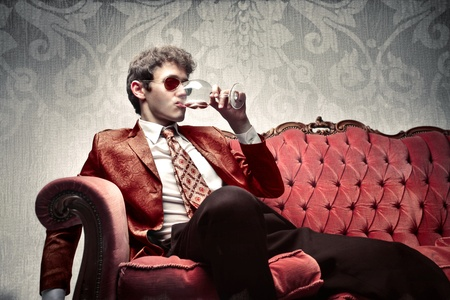 Young man sitting on a sofa and drinking a glass of wine