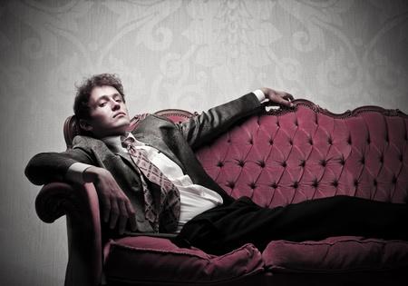 Handsome elegant young man lying on a velvet sofa