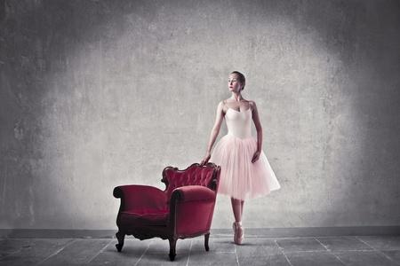 Ballerina standing beside an armchair