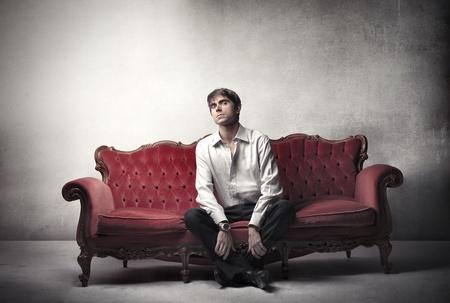 Handsome man sitting on a velvet sofa