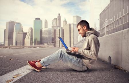 Photo pour Young man sitting on a city street and using a laptop - image libre de droit