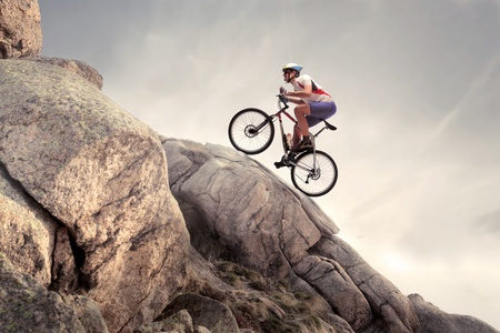 Cyclist climbing up a rock with his mountain bike