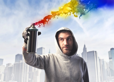 Young man spraying colored paint with cityscape in the background