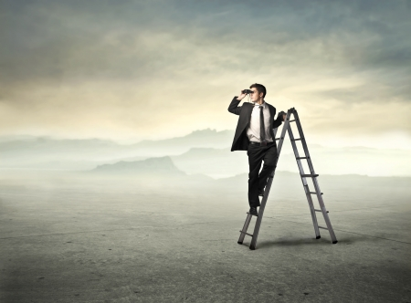 Businessman on a ladder using binoculars in a desert