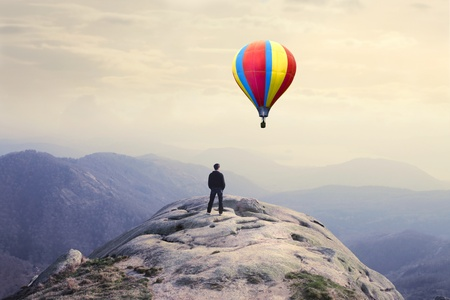 Businessman on a peak with hot-air balloon in the background