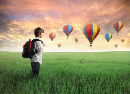 Child carrying a backpack on a green meadow with hot-air balloons in the background