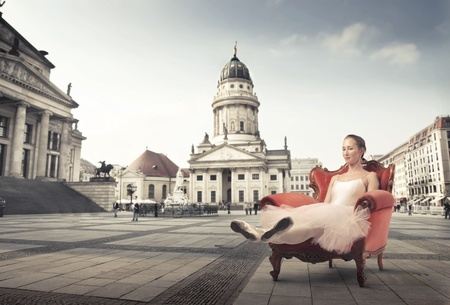 Ballerina relaxing on an armchair with museum in the background