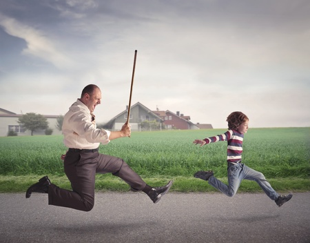Angry father running after his son with a stick
