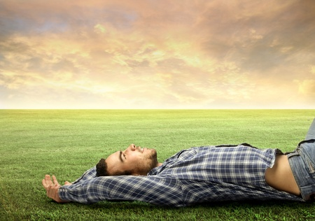 Young man relaxing on a green meadow