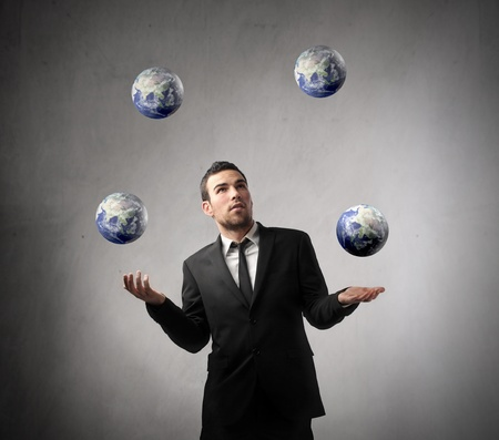 Young businessman juggling with earth planets
