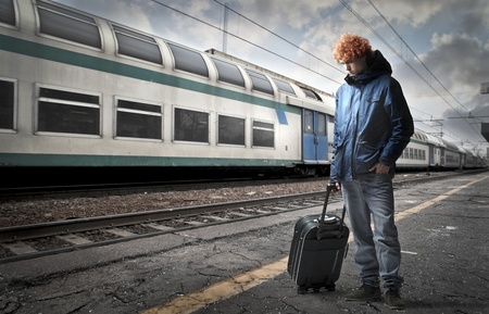 Photo pour Young man carrying a trolley case on the platform of a train station - image libre de droit