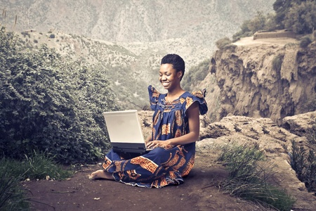 Smiling african woman in traditional dress sitting on a rock and using a laptop