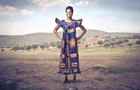 Foto de Smiling african woman in traditional dress in a desert - Imagen libre de derechos