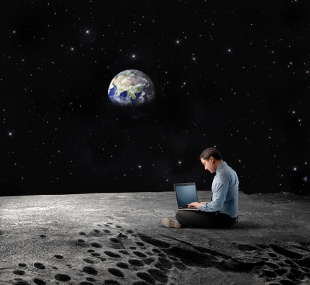 Businessman sitting on the Moon and using a laptop with Earth Planet in the background